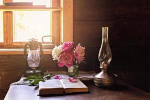 stilleben av vintageartiklar och en bukett pioner på ett bord vid fönstret foto