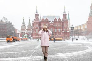 en vacker ung flicka i en rosa jacka går längs manezhnaya torget i Moskva under ett snöfall foto
