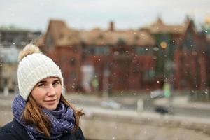 porträtt av en ung vacker glad leende flicka på bakgrunden av staden foto