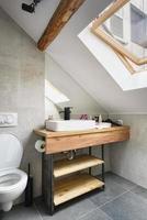 vinden lägenhet, modernt badrum, lägenhet inredning med gamla rustika träbjälkar och möbler, elegant italiensk granit ceramica. foto