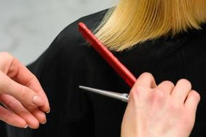 kvinnlig frisör håller i handen mellan fingrar blont hår, kam och sax på nära håll, räta ut hårspetsar. foto