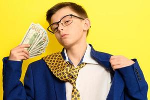 en kille i en stor klassisk kostym på gul bakgrund innehar en utländsk valuta, ett barn i glasögon och en kostym med slips. foto