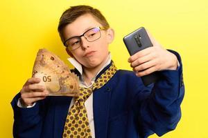 framgångsrikt och rikt barn som tar en selfie med pengar, porträtt av en pojke i kostym på gul bakgrund. foto