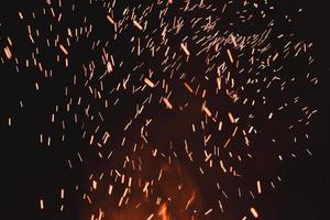 närbild av gnistor från eld, gnistor på svart bakgrund, extravaganza av eld, magi med gnistor. foto