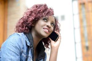 vacker svart kvinna i urban bakgrund på telefonen foto