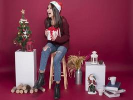 härlig jultomteflicka i studio på röd bakgrund, julkoncept foto