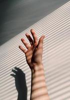 en vy av skuggor från persienner på en persons arm foto