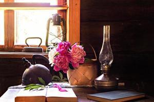 stilleben av vintageartiklar och en bukett pioner på ett bord foto