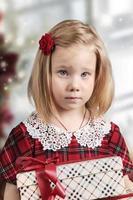 en liten flicka i en röd klänning håller en presentask i sina händer foto