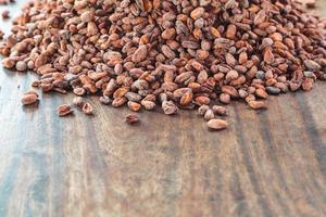 rå kakaobönor på ett träbord foto