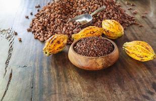 kakao nibs och kakaofrukt på träbord foto