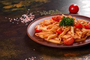 läcker färsk pasta med tomatsås med kryddor och örter på en mörk bakgrund foto
