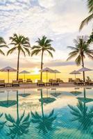 paraply och stol runt poolen i hotellresorten med soluppgång på morgonen foto