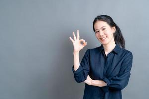 ung asiatisk kvinna som ler och visar ok tecken foto