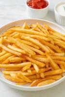 pommes frites med gräddfil och ketchup foto