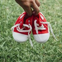 söta röda små dukskor på gräset foto