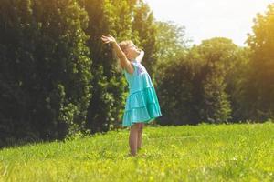 liten flicka i parken med hennes armar öppna livskoncept foto