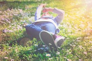 liten flicka tycker om dagen i parken och lägger på gräs foto
