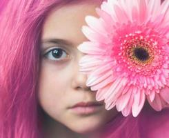 porträtt av en liten flicka med rosa hår och rosa blomma över ögat foto