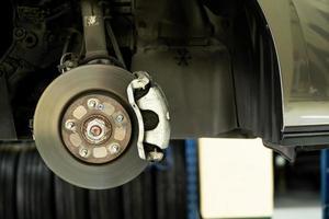 skivbil på nära håll - mekaniker som lossar bildelar medan du arbetar under en lyft bil foto