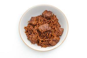 jjapaguri eller chapaguri, koreanska svarta bönor kryddiga nudlar med nötkött på vit bakgrund foto