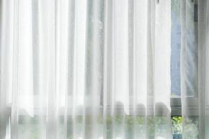 vit gardin vid fönstret med solljus foto