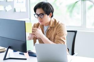 asiatisk affärsman som i regeringsställning arbetar med datorn foto