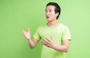porträtt av asiatisk man i grön t-shirt poserar på grön bakgrund foto