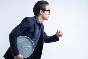 stående av den asiatiska affärsmannen som håller klockan foto