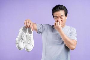 asiatisk man som håller sneakers på lila bakgrund foto