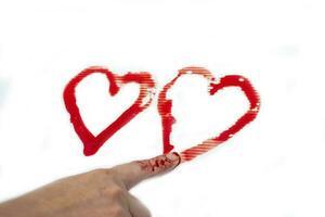 använd ditt finger för att rita ett hjärta med blod på vit bakgrund foto