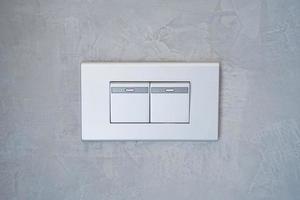 grå ljusbrytare på betongväggen. foto