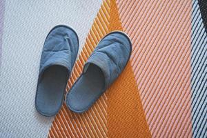 grå tofflor på mattan. foto