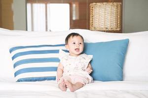 söt leende flicka sitter på sängen. foto