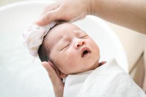mamma tvättar babyhår. mamma rengör sitt babyhår. foto
