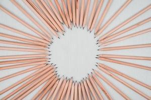 träpennor ordnade i en cirkel på det vita bordet. foto
