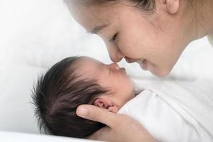 närbild ung asiatisk mamma kysser hennes nyfödda barn. mammas kärlek nyfödda. foto