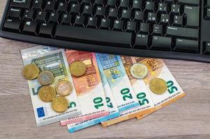 europengar av olika valörer och datorns tangentbord foto