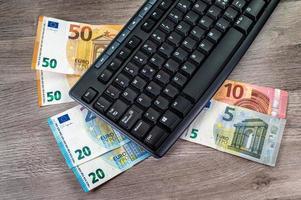 eurosedlar av olika valörer och datortangentbord på träbakgrund foto
