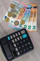 europengar av olika valörer och miniräknare foto