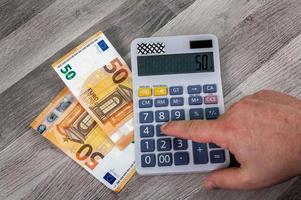 Räkningar på 50 euro med miniräknare i närheten foto
