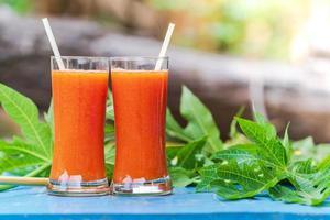 papaya juice på ett träbord foto