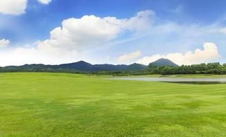 golfbana med grönt gräs och träd i vacker park under den blå himlen foto
