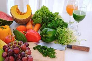 diverse färska mogna frukter och grönsaker på bordet vid vit gardinbakgrund, foto