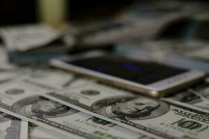 stapla pengar på en bunt med 100 US-dollar sedlar på suddig bakgrund foto