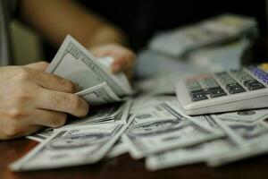 affärsmän kvinnor räknar pengar på en bunt med 100 dollar sedlar foto
