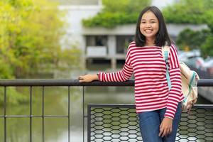 asiatisk studentflicka som står i parken en solig sommardag foto