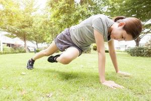 vacker sportig kvinna gör övningar i green park foto