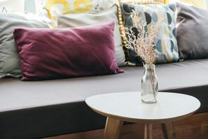 blomma vas på bordsdekoration med kudde och soffa foto