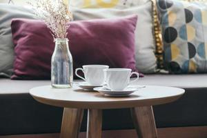 vit kaffekopp med blomvas på bordsdekoration med kudde på soffan foto